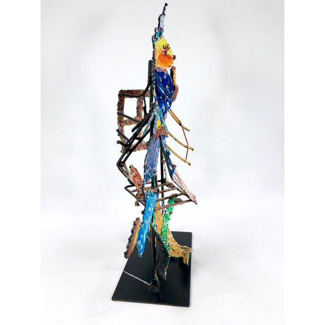 Colorful 1983 metal sculpture of a person surrounded by abstract creatures and architecture. The piece is signed by neo-...