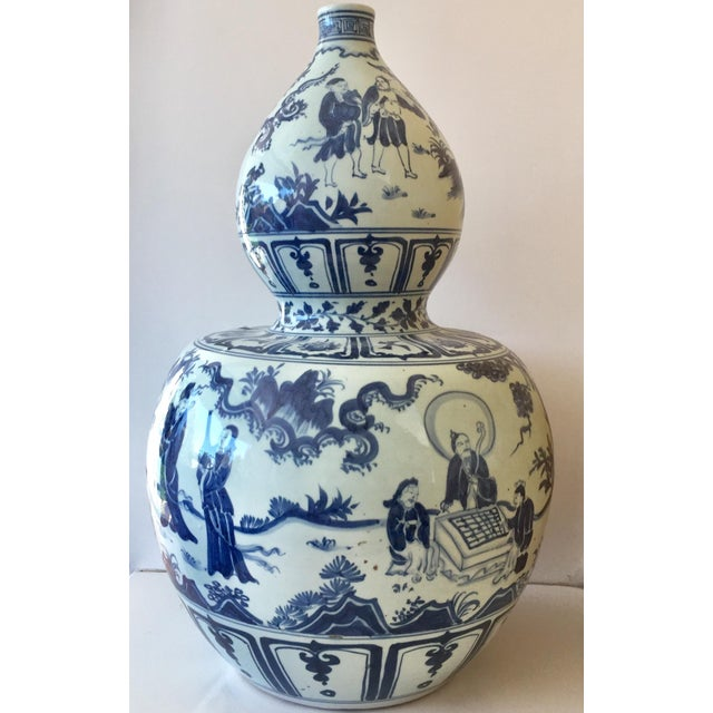 A stunning pair of large porcelain vases depicting scenes of figures in everyday life set in nature