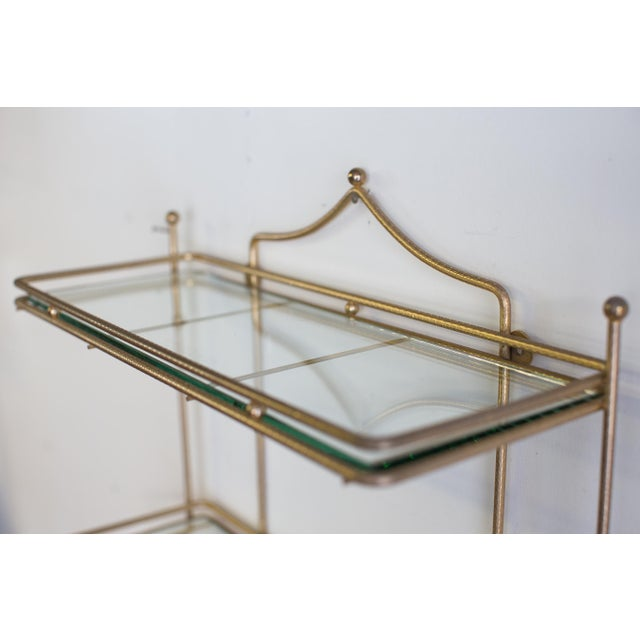 A sleek, minimal, mid-century, brass and glass wall shelving unit. (Say that 3 times fast!) This beauty would be great in...
