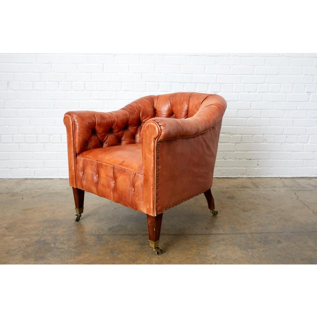 Spectacular pair of English leather Chesterfield style club chairs or tub chairs. Featuring a beautifully aged and faded...