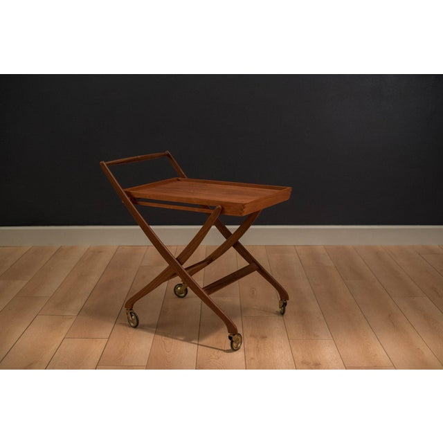 Mid-Century Danish bar cart or serving tray in solid teak. This well-crafted piece displays unique scissor legs and a...