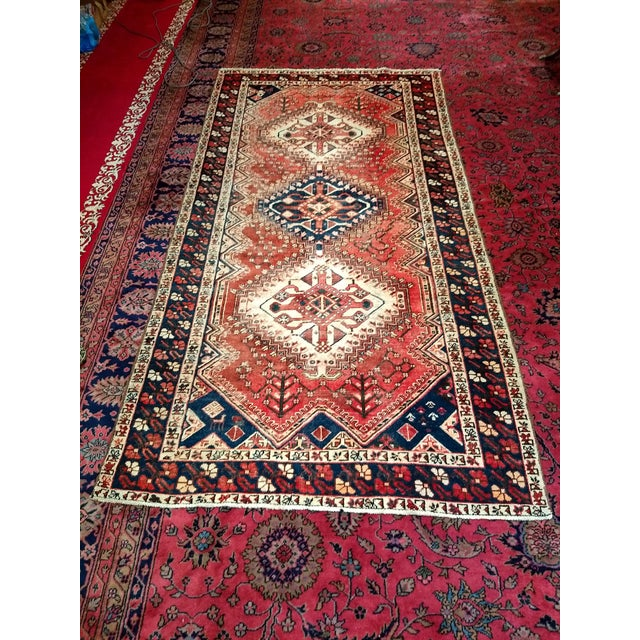 This gallery size rug from the Shiraz region of western Persia comes with traditional three vertical medallions. The use...