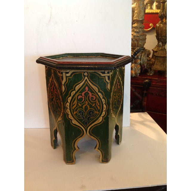 Petite and endlessly charming chair side table / drink table with Moorish hand painted design in vivid colors .