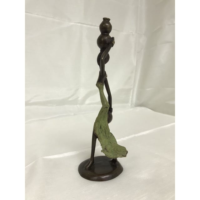 This is a contemporary hand crafted bronze African figurine depicting a woman carrying water.