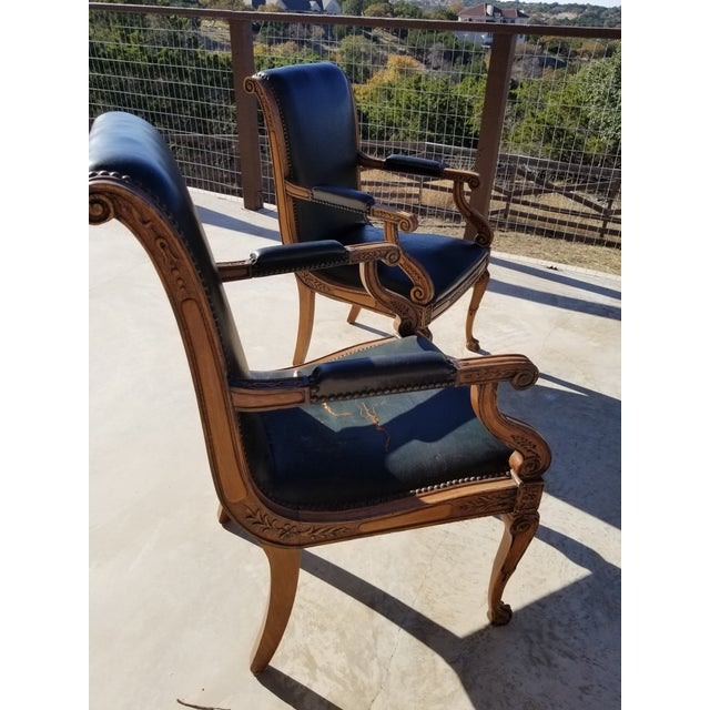 Pair of 1920's Hollywood regency or french empire style arm chairs with distressed blackish leather with brass tacs. These...