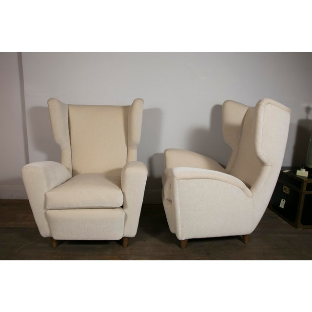 A pair of wingback lounge chairs Newly re upholstered with ivory mohair velvet (Nobilis). Elegant chairs in the style of...