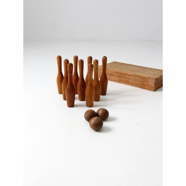 A beautiful antique table top bowling game set. It includes nine small wood clubs or skittles, three small wood balls and...