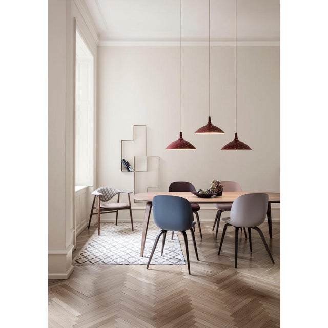 Paavo Tynell '1965' pendant lamp in red. Originally designed by Paavo Tynell in 1947, this authorized GUBI re-edition is...