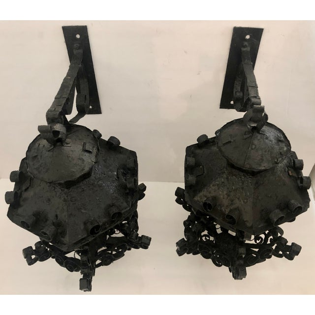 Cute pair of iron and glass outdoor sconces. Very decorative. Metal shows a lot of wear underneath painting. Need new...