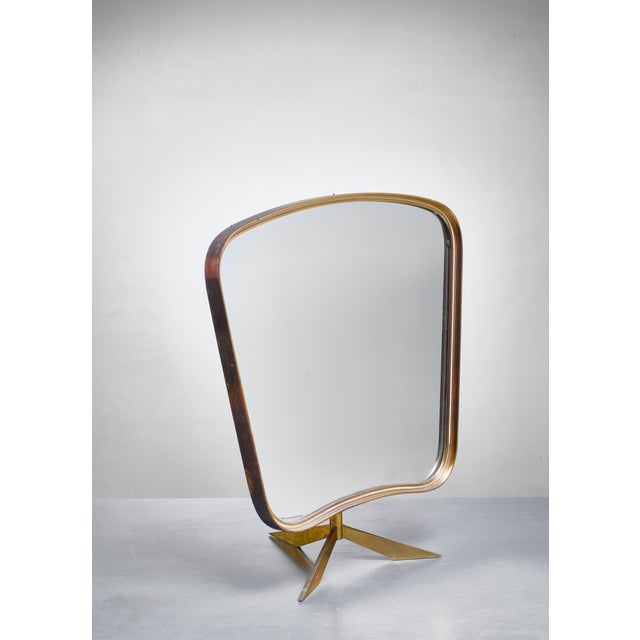 An adjustable brass console mirror with a curved frame on a tripod foot. The mirror can be positioned with the concave...