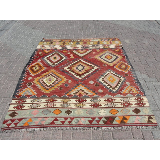 Vintage handwoven Turkish kilim rug. The kilim is nearly 50 years old. It is handmade of very fine quality natural wool in...