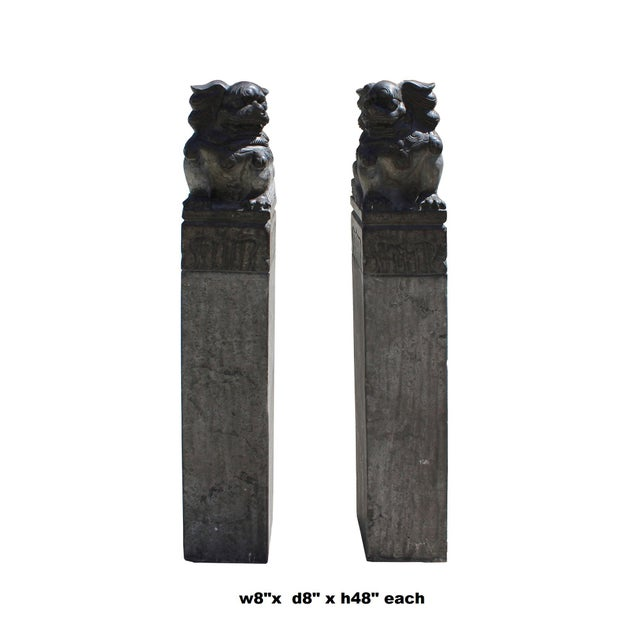 This is a pair of traditional Chinese slim stone pole statues with Foo dogs carving on a plain tall base. They have a...
