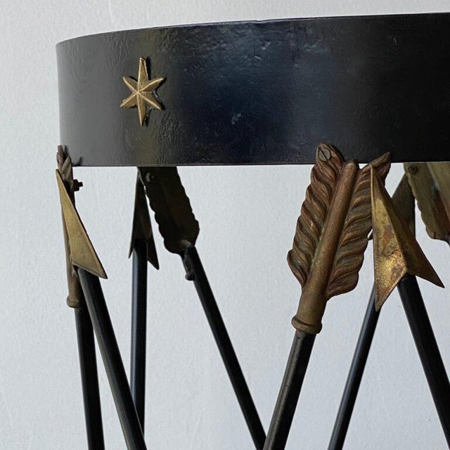 Pair of arrow and star-motif side tables with glass top. Bases are metal. Height: 28.5 in Diameter: 15.5 in