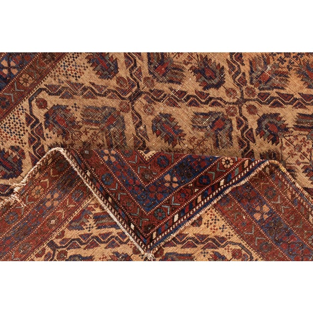 A beautiful Antique Persian Afshar Handmande Wool Rug with a geometric Distressed design on a tan field with brown and...