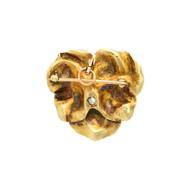 A fine antique 14K gold enameled pansy pin with a prong set old European cut diamond in the center. The diamond is...