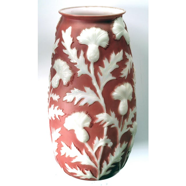 A tall American 1960's sculpted art glass vase of frosted coral glass with raised meandering thistle branches; 'Phoenix...