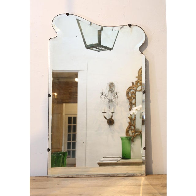 Asymmetrically-shaped Art Nouveau mirror with beveled edge. Backed by a thick painted wood back. Circa 1900-1920, France.