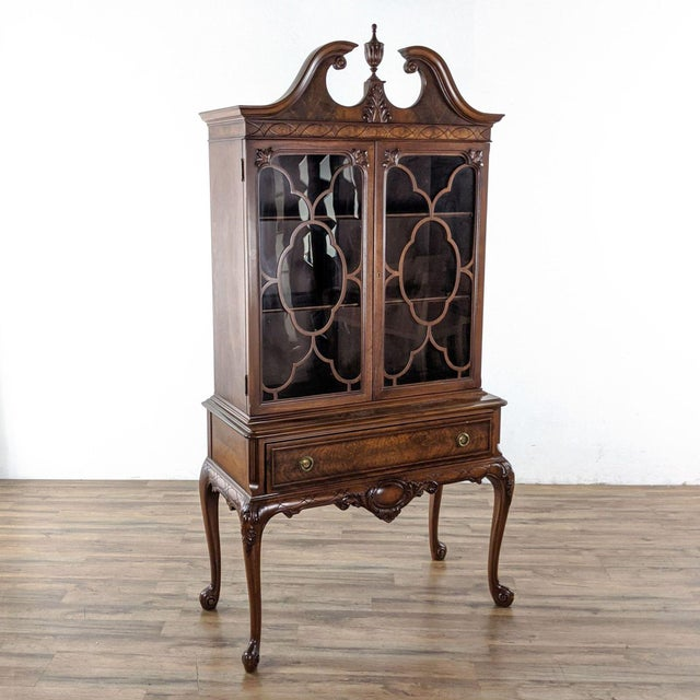 A circa 1920s vintage china cabinet, in mahogany. It has a scrolled arch pediment, an upper hutch with three shelves...