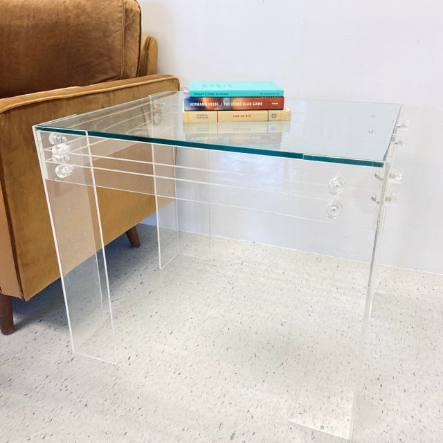 Mid-century side or coffee table made of lucite frame with glass inset top surface. Made in the 1970s.
