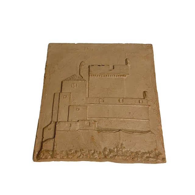 A hand carved antique tile with a carved castle. Made in the early 20th century.