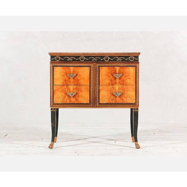 Beautiful petite-scale French-Regency style commode featuring a flame mahogany veneered front with brass cherub drawer...