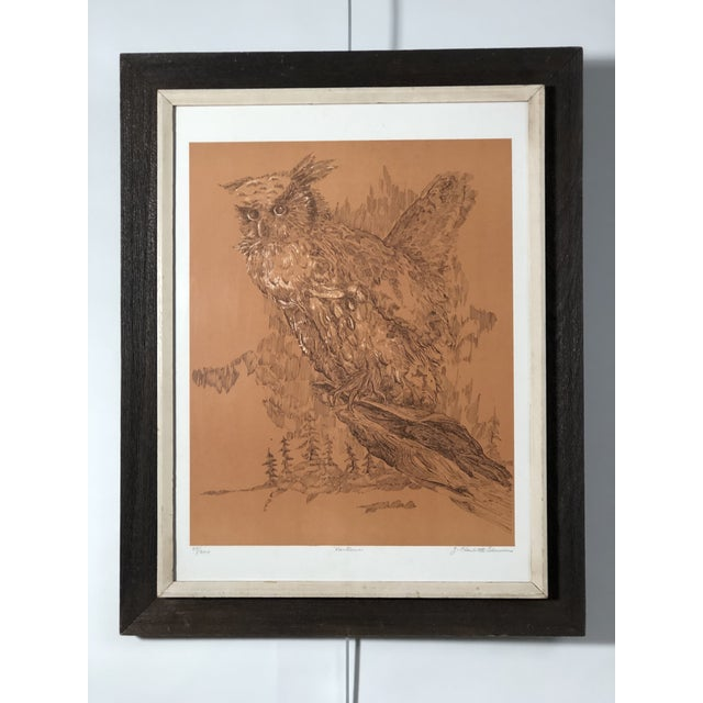 Finely detailed midcentury portrait of an owl in its habitat. The lithograph has a light brown background, black details,...