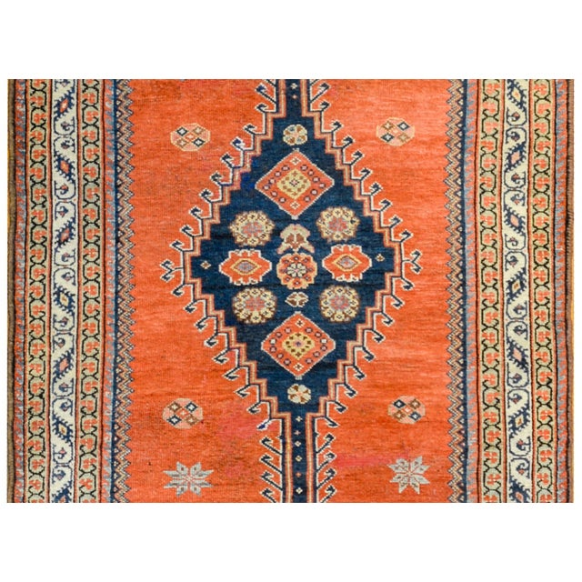 A wonderful late 19th century Persian Azari runner with four large indigo medallions with stylized flowers on a crimson...