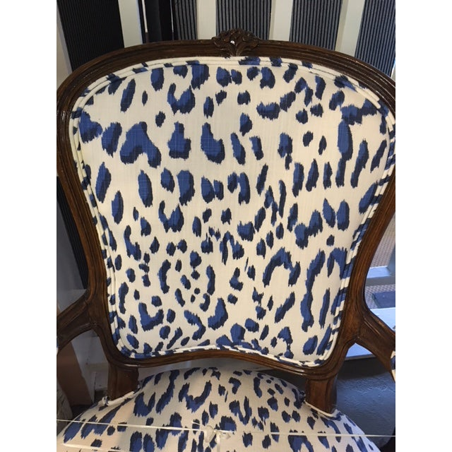 A pair of newly upholstered Bergere chairs, upholstered in Schumacher blue leopard linen with with arm rests covered in...