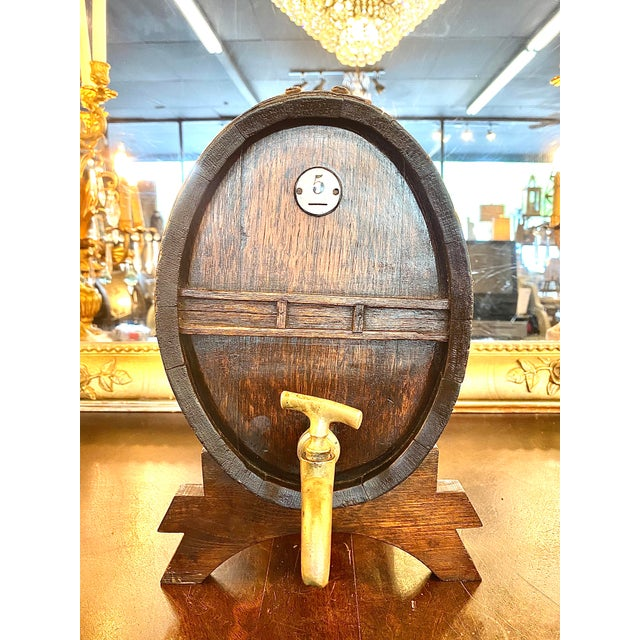 19th. C. French antique oak Cognac barrel. This oval wood barrel with brass and iron rims sits on a separate base and...