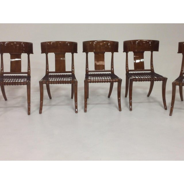 A set of 6 Modern dining chairs. The chairs are in the manner of Robsjohn Gibbings. The Klismos style dining chairs are...