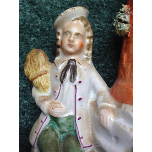 An antique English Staffordshire figurine depicting a beautiful young women wearing a pink dress and a hat with a handsome...