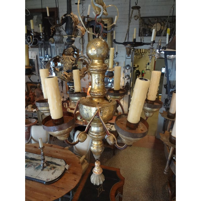 Charming small carved gilt wood Italian six lights chandelier . US wired. Iron arms are painted in a dark red with tole...