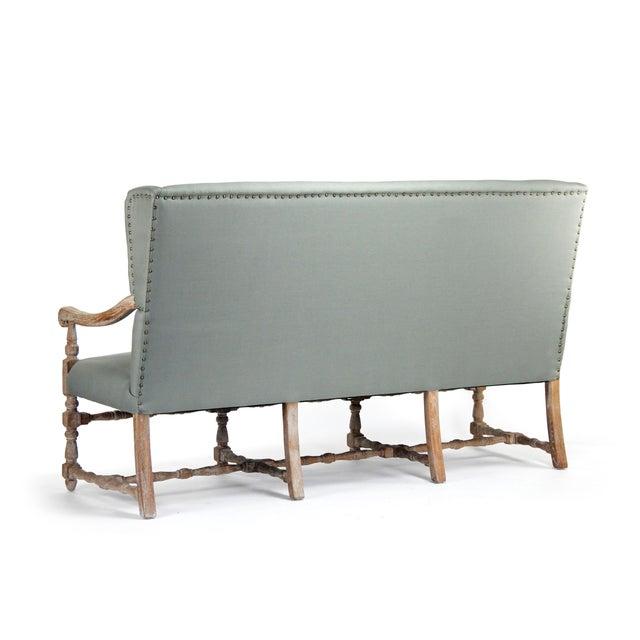 Wing back bench upholstered in sage linen on limed grey oak frame.