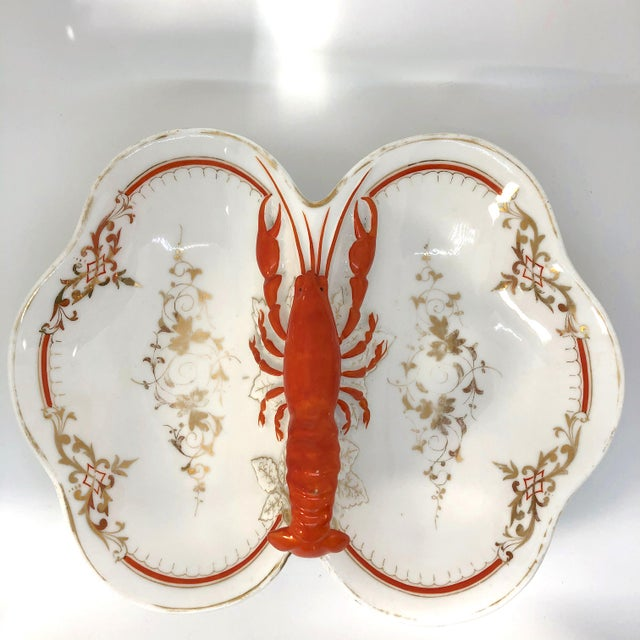Trompe l'oeil, double sided serving dish features a stunning hand painted lobster with gilt filigree edging detail....