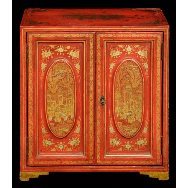 Chinese export miniature red lacquered table top cabinet with gilded decoration of figures having tea, pogodas, trees and...
