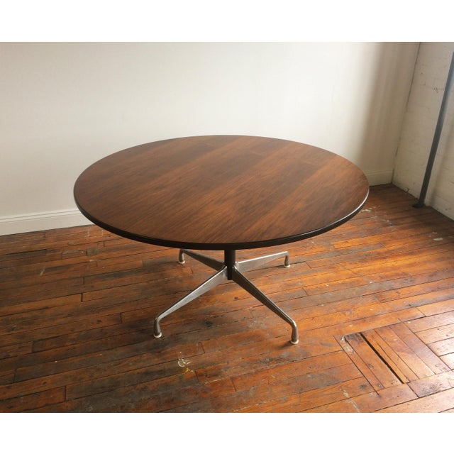 Large, round Aluminum Group table with metal base, designed by Charles & Ray Eames for Herman Miller. The table top has...
