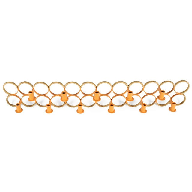 A rare wall-mounted candelabra comprised of two dozen orange lacquered wrought iron rings with rush twisted partially...
