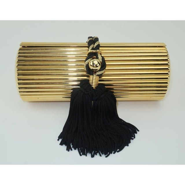 This Walborg handbag is a precious bauble as fun to display as it is to carry. The gold metal cylinder shape has fluted...