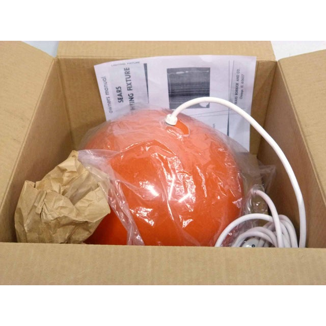 A mid century new old stock orange dome aluminum pendant swag lamp with white white glass globe. The light comes in...