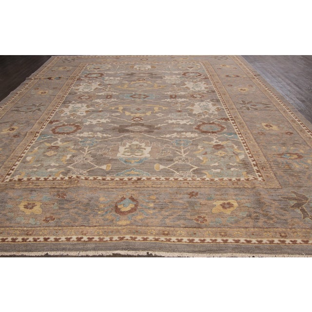 A hand-knotted Sultanabad rug with a geometric design on a brown field. Accents of ivory, beige and blue throughout the...