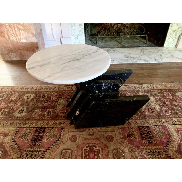 Stacked black marble base acts as a sculpture to the rotating, off-center, round, Carrara marble top. Vintage, sturdy, and...