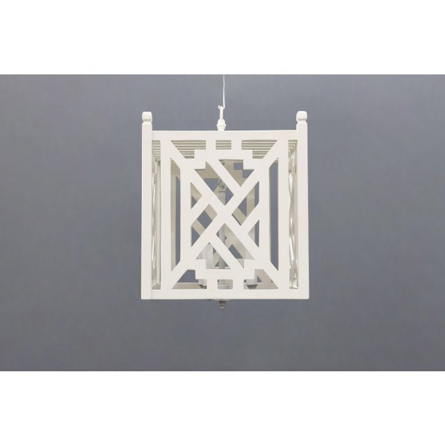 White painted lantern. Modern geometric shapes on a cube body.