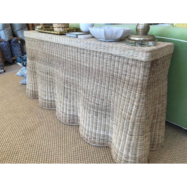 Rattan scalloped console with a natural finish. Perfect for adding a touch of texture or organic shape to any living space.