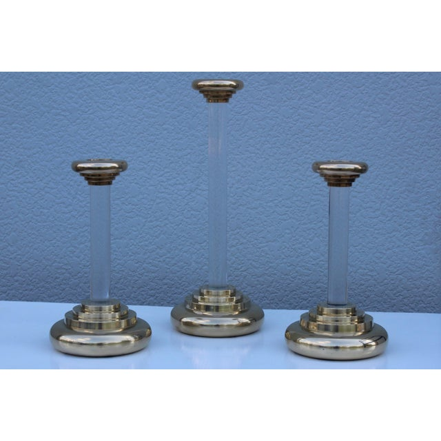 """Large set of three 1980s modern Lucite and brass candleholders. The two smaller candleholders height is 12""""."""