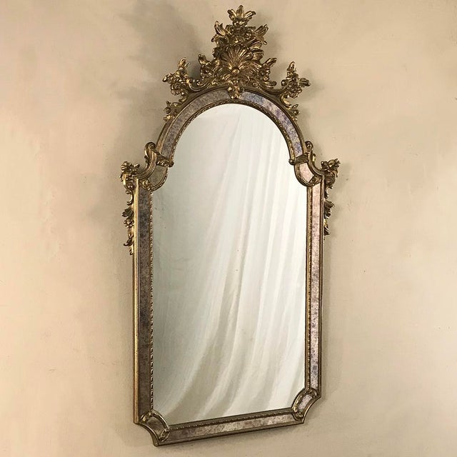 Mid-Century Italian Venetian Gilded Mirror features exquisite hand-sculpting and painstaking gilding to create a...