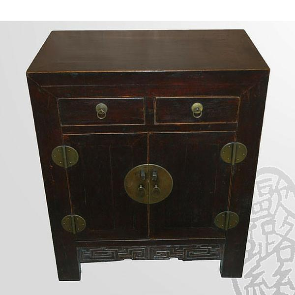 The large round hardware of this piece stands out against the natural dark wood tone. Two small drawers over one cabinet...