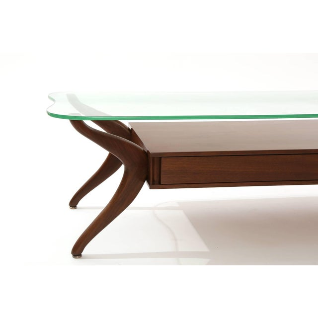 Free-form walnut and glass coffee table circa late 1950s. This example has solid walnut legs, two drawers for storage and...