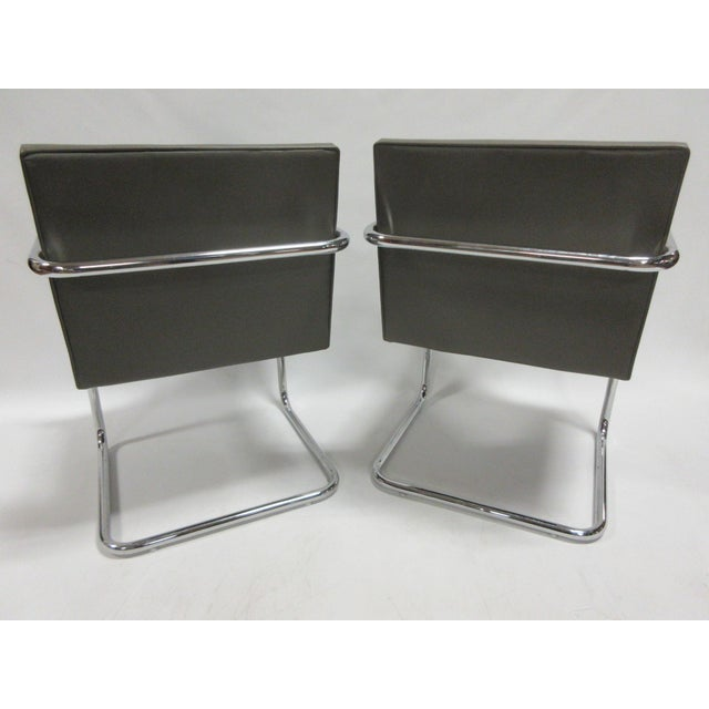 A pair of BRNO Model 504 chairs by Mies van der Rohe upholstered in beautiful grey vinyl upholstery. The chairs feature a...