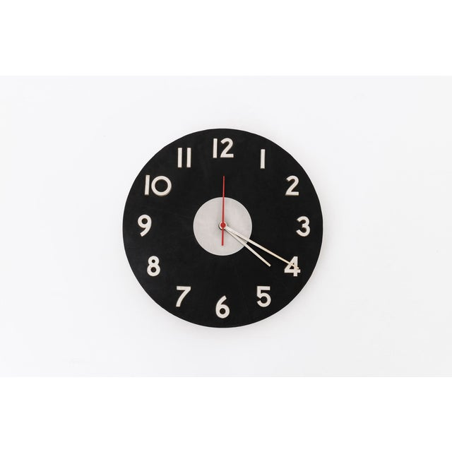 George Nelson wall clock of Howard Miller. Model No. 2504. This clock has a wooden back with leather face and aluminium...