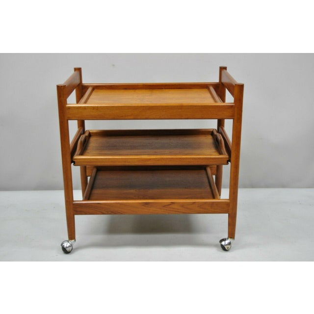 Vintage mid century Danish modern teak rolling bar cart table by Dixie. Item features rolling casters, pull out serving...